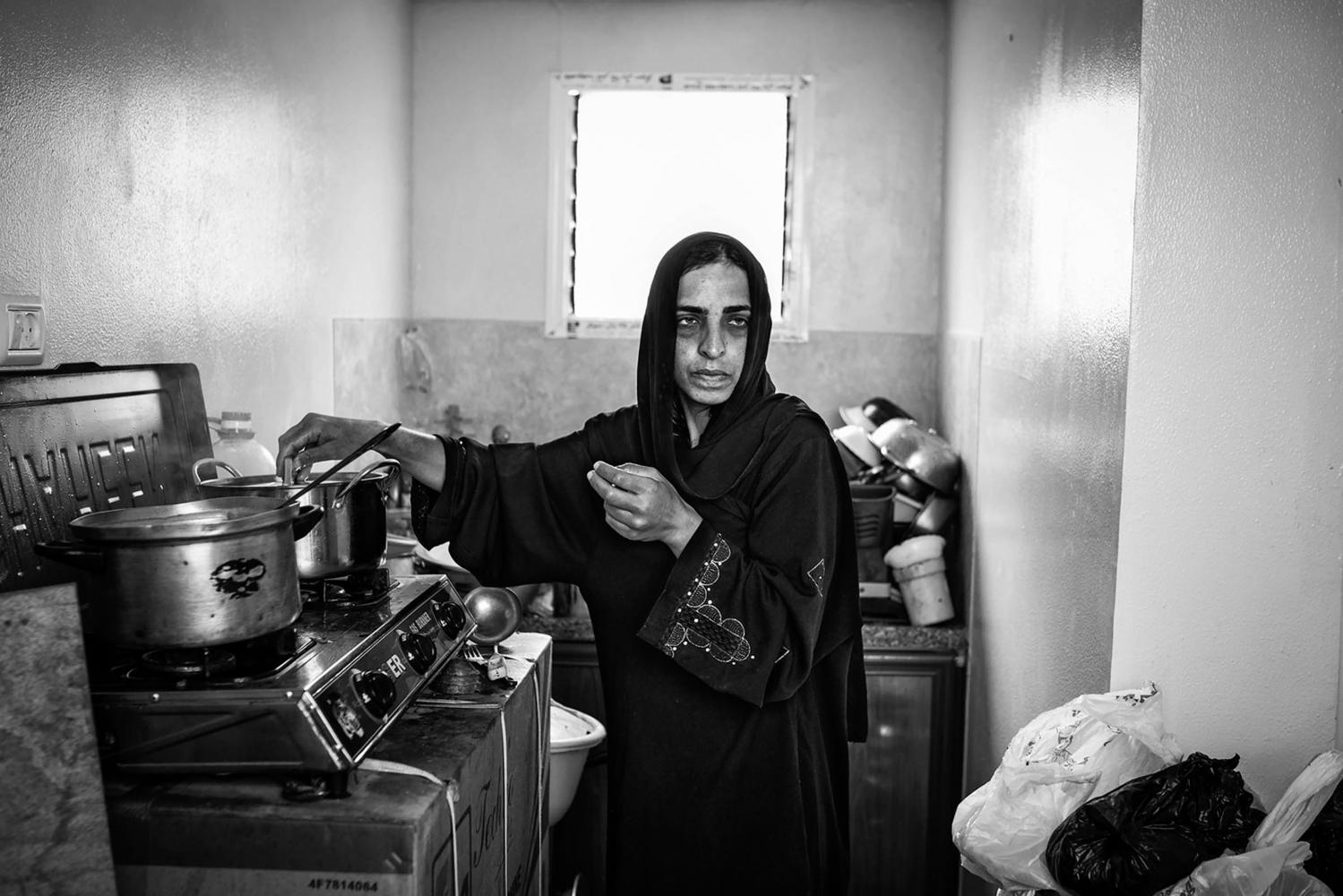 Gaza, Khuzaa: Sabrine Al Najar prépare le repas à l'intérieur de la petite cuisine de son conteneur. 31/10/14