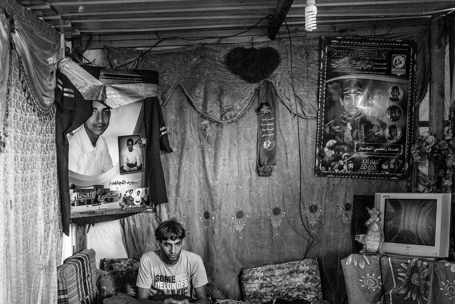 Gaza, Khuzaa: Ahmed Al Najar est assis dans le salon du conteneur où vit sa soeur et sa mère. Au-dessus de lui, des photos de son frère tué pendant la guerre de 2014. 09/08/15