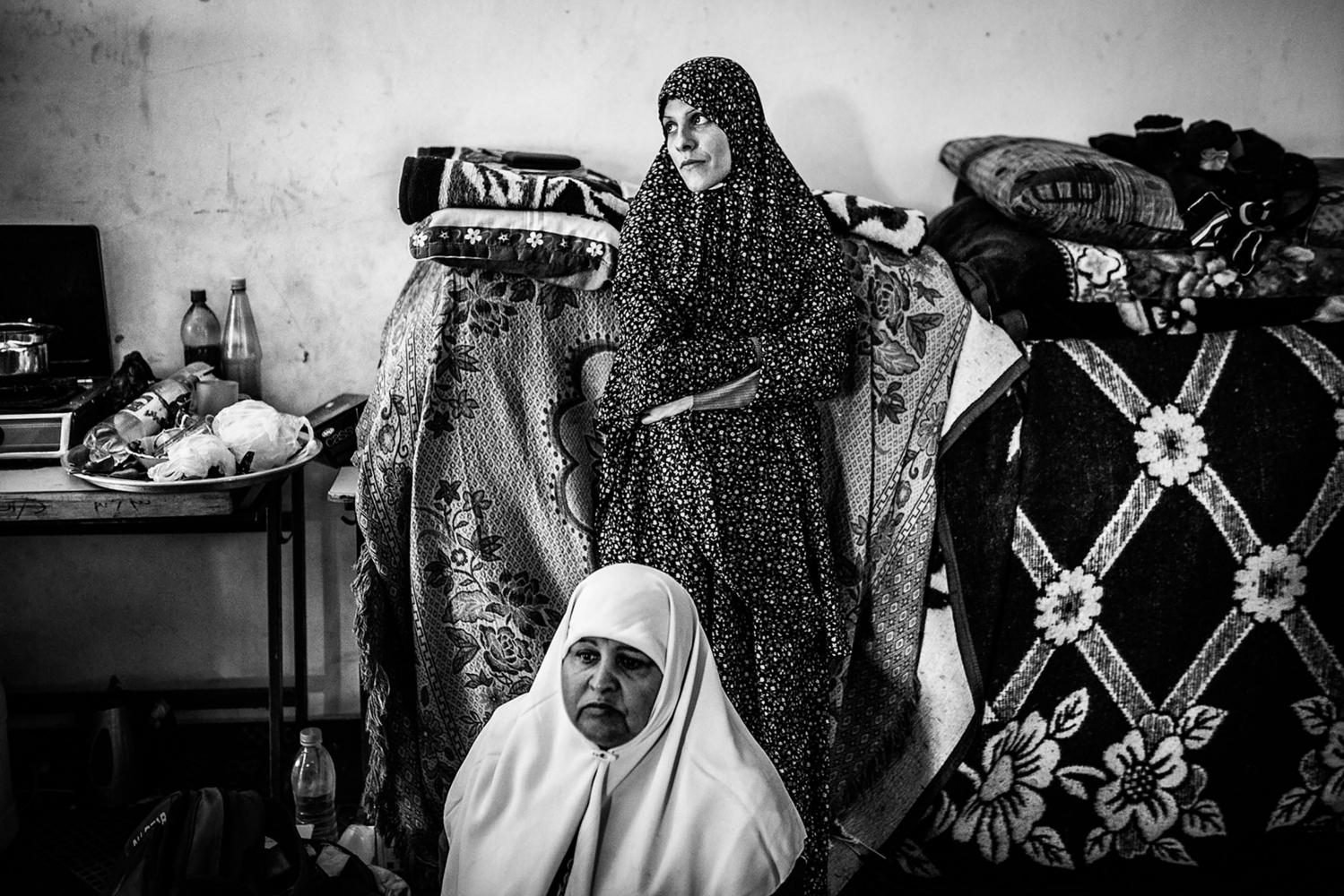 Gaza, Beach Camp: Shadia Alsabagh et sa belle-mère debout dans la salle de classe où elles se sont installées au mois de septembre 2014. Leur maison à Beit Laya a été détruite le premier jour de la guerre de l'été 2014.  22/10/14