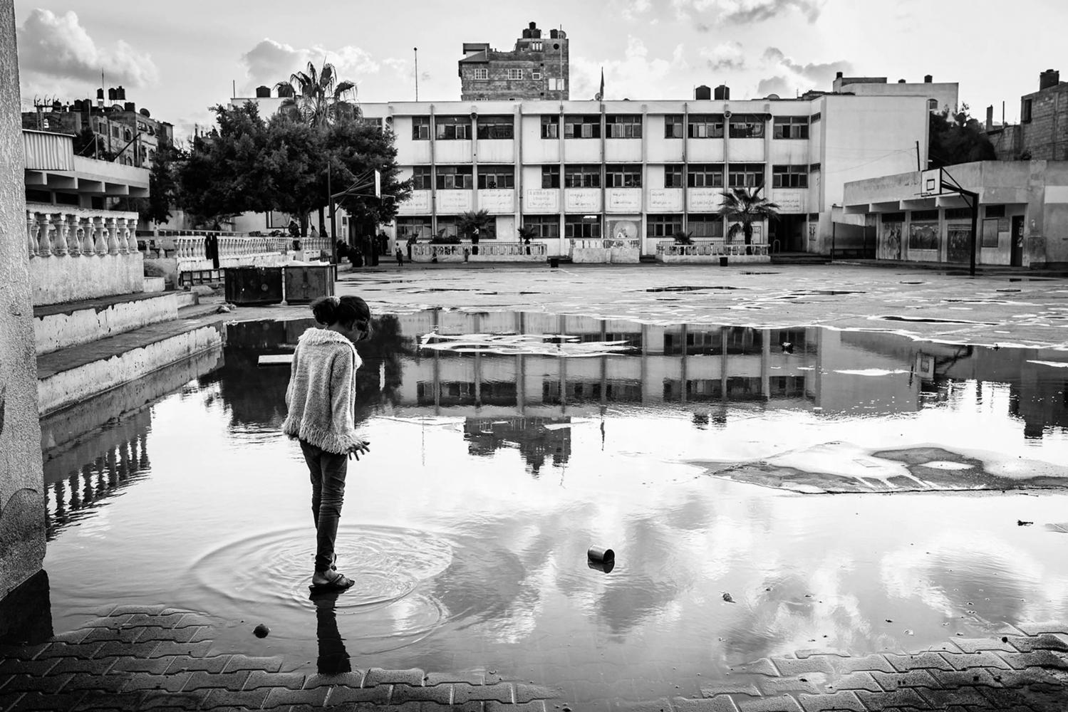 Gaza, Beach Camp : Dalia Alsabagh, 10 ans, marche dans de l'eau de la cour de l'école de l'UNRWA,où elle vit avec sa famille, après que de fortes pluies soient tombées sur Gaza. 04/11/14