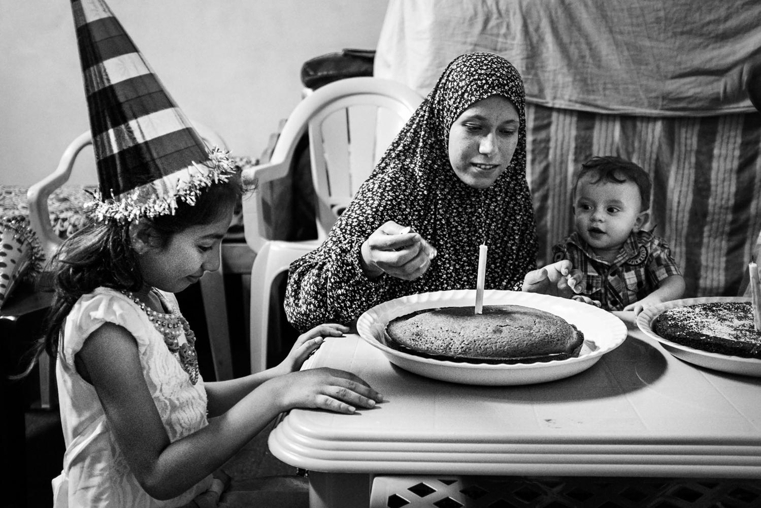 Gaza Shejaya: Yamen Al Batneeny célèbre son premier anniversaire avec sa tante et sa cousine. Il est né pendant la guerre 2014 tandis que sa maison était déjà complètement détruite par un raid aérien israelien. Pour son anniversaire, ses grands-parents ont obtenu la nouvelle que la reconstruction de sa maison commencera normalement la semaine d'après. 12/08/15